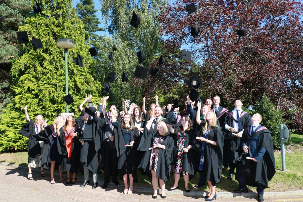 Graduates enjoying sunshine and throwing mortar boards
